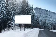 Empty billboard for advertising poster, on the background of snowy fir-trees. Winter season in a mountainous area. Empty billboard for advertising poster, on Stock Photos