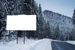 Empty billboard for advertising poster on the background of snowy trees. Winter season in a mountainous area.  Stock Photos