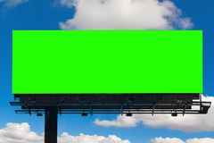Empty billboard with chroma key green screen, on blue sky with c. Louds, advertisement concept royalty free stock photography