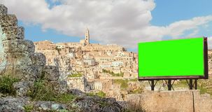 Empty billboard with chroma key green screen, panoramic view of typical stones Sassi di Matera and church of Matera, European stock video footage