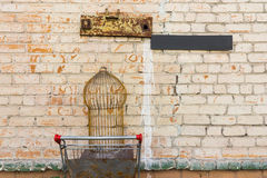 Empty bird cage in shopping cart in brick wall Stock Photo