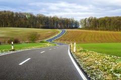 Empty black asphalt road between green fields Royalty Free Stock Photos