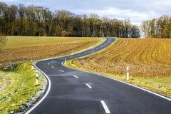 Empty black asphalt road between green fields Stock Photography
