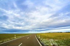 Empty black asphalt road between green fields Stock Image