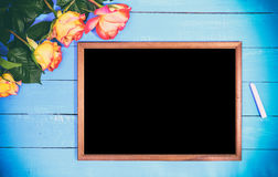 Empty black board and bouquet of yellow roses Stock Photo