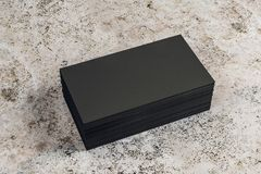 Empty black business cards on desktop. Empty black business card stack on concrete desktop. Info, address and message concept. Mock up, 3D Rendering royalty free illustration