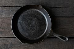Empty black cast iron pan isolated on dark painted wood from abo stock images