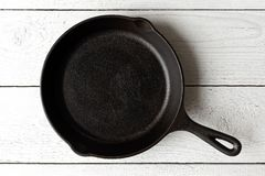 Empty black cast iron pan isolated on white painted wood from ab royalty free stock image