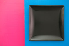 Empty black ceramic dish on over blue and pink background, squar Stock Images