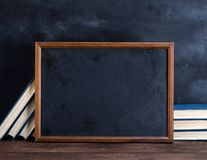 Empty black chalk drawing frame and stack of books stock photo