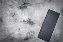Grey grunge textured background and black stoun board. Empty black cutting board of stone on a gray concrete grunge textured background. Copy space Stock Image