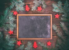 Empty black frame on a brown wooden background. In the middle of green spruce branches and New Year`s decor Stock Images