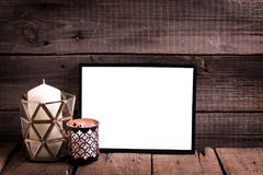Empty  black  frame and  candles  on  aged wooden background. Place for text. Mock-up for design. Minimalism style Royalty Free Stock Image