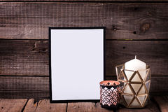 Empty  black  frame and  candles  on  aged wooden background. Place for text. Mock-up for design. Minimalism style Royalty Free Stock Images