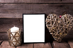 Empty black  frame, decorative heart  and  candles  on  aged woo. Den background. Place for text. Mock-up for design Royalty Free Stock Images