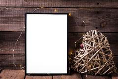 Empty  black frame and decorative heart with twinkle  light  on. Aged wooden background. Place for text. Mock-up for design Stock Image