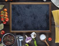 Empty black frame and ingredients for cooking pasta. On a brown wooden table, copy space royalty free stock photo