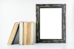 Empty black frame and old books on a white background. royalty free stock photography