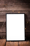 Empty   black  frame with twinkle light  on  aged wooden backgro. Und. Place for text. Mock-up for design Royalty Free Stock Images