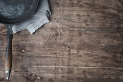 Empty black frying pan on a brown wooden table. Black frying pan on a brown wooden table, empty space Stock Images
