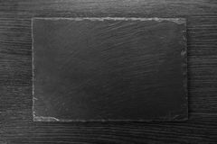 Empty black kitchen board. Close-up on a wooden background Royalty Free Stock Photo