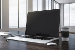 Empty black laptop. Close up of empty black laptop on wooden desktop with coffee cup and supplies. Blurry office with sky view background. Mock up, 3D Rendering royalty free illustration