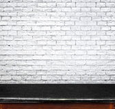 Empty black marble table and white brick wall in background. pro Stock Image