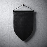 Empty black pennant hanging on concrete wall.High detailed texture material.  Ready for your business information. Abstract backgr Royalty Free Stock Photo