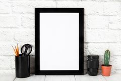 Empty black photo frame on wooden shelf or table. Mockup with copy space. royalty free stock image