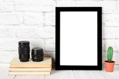 Empty black photo frame on wooden shelf or table. Mockup with copy space stock photos