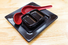 Empty black plate dish and spoon on wooden background Royalty Free Stock Image
