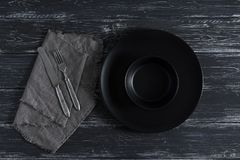 Empty black plate, fork and knife on napkin, rustic dark background. View from above, horizonal projection.