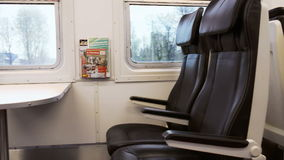 Empty black seats in moving express train. Panning shot of comfortable empty seats with tables in moving express train stock video footage