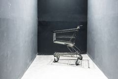 Empty black shopping cart. Stand alone in black corner Royalty Free Stock Image