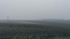 Empty black soil field with pylons in heavy fog Stock Photo