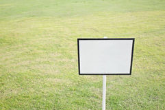 Empty black and white sign board on green grass Stock Photos