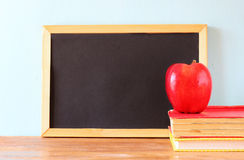 Empty blackboard , apple and stack of books. back to school concept. Royalty Free Stock Images
