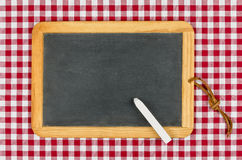 Empty blackboard with chalk on a checkered table cloth. Empty blackboard with chalk on a red checkered table cloth Royalty Free Stock Image