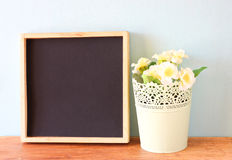 Empty blackboard and flowerpot over wooden shelf Stock Photography