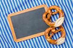 An empty blackboard with pretzels on a bavarian diamond pattern Stock Image