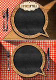 Empty Blackboard for a Restaurant Menu. Two empty blackboards in the shape of speech bubble on a table with red and white checkered tablecloth and silver cutlery vector illustration
