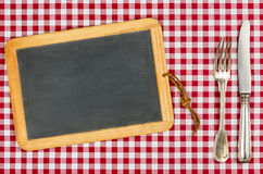 Empty blackboard with silverware on a tablecloth Royalty Free Stock Image