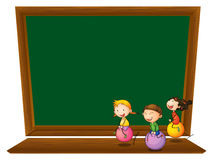 An empty blackboard with three playful kids Royalty Free Stock Photo