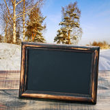 Empty blackboard with wooden frame on the background of winter f Royalty Free Stock Photography