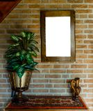 Empty blank cut out wooden painting or mirror frame hanging on a brick wall above a table cabinet with a carpet rug decorated with. A empty blank cut out wooden stock photos