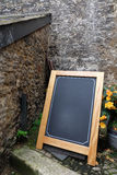 Empty blank frame wooden blackboard easel stand decorate with flowers on floor and grunge wall background. Royalty Free Stock Images