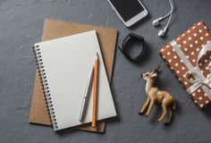 Empty blank notebook, gift box, christmas decoration reindeer, phone on office desk top view. Royalty Free Stock Images