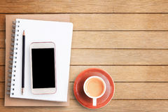 Empty blank paper notebook and smart phone on brown wooden table Stock Image