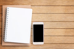 Empty blank paper notebook and smart phone on brown wooden table Stock Images