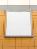 Empty blank square white advertising billboard on orange tiled wall Stock Photos